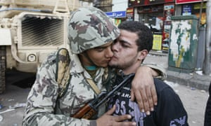 An Egyptian civilian kisses an army sold