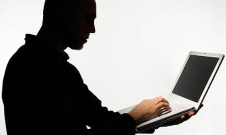 Silhouette of man using laptop