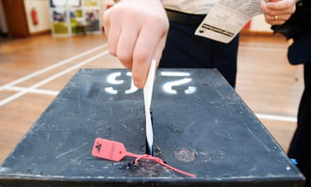 A voter places his voting card into a ballot box