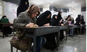 Women fill in their ballots during Iran's parliamentary election, at a mosque in southern Tehran