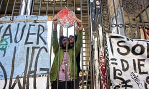 Artists from the Tacheles art community shout slogans from behind a gate