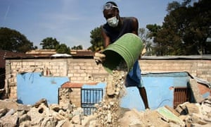 Haitians clean up the debris in a house