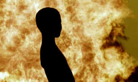 A nigerian child is silhouetted against the gas flare at Utorogu Shell facility in nigeria's delta