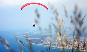 A paraglider flies over the beach of Vlore