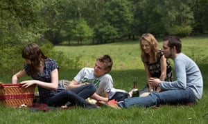 Two couples having a picnic in the park