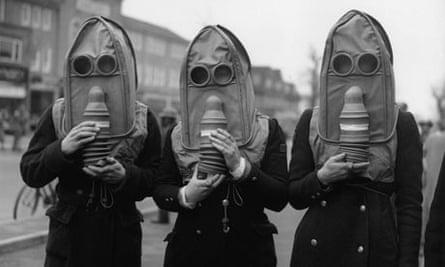Three air raid wardens wearing gas masks