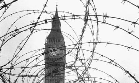 Big Ben partially obscured by barbed wire.