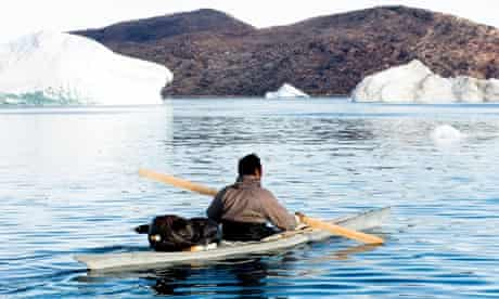 Inuit narwhal hunter paddling kayak on a narwhal hunt at  Inglefield Fjord near Qaanaaq Greenland