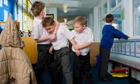 Aggressive school boys rough housing in classroom