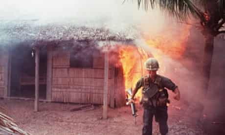 A US soldier hurries away after setting fire to a thatched house during the Vietnam War.