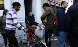 People take goods from a destroyed store