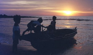 CHILDREN PLAY ON A FISHING BOAT AT SUNSET ON AN INDONESIAN ISLAND