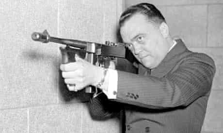 FBI director J Edgar Hoover aims machine gun