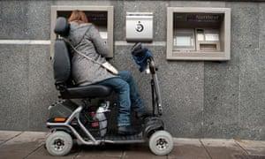 Woman in wheelchair using an ATM