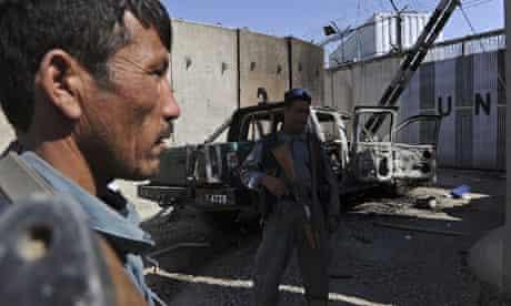 Afghan policemen keep watch near the wre