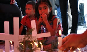 A girl looks at a person placing a candl