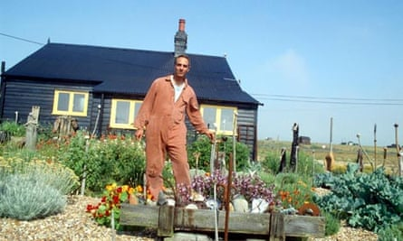 Derek Jarman stands in the driftwood garden at the front of Prospect Cottage
