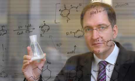 Peter Seeberger holds a flask of artemisinin
