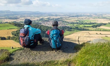 ikers overlooking Great Ayton village from top of Roseberry Topping in North Yorkshire