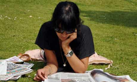 woman reading newspapers in park