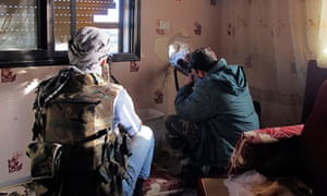 Free Syrian Army fighter points weapon out of house
