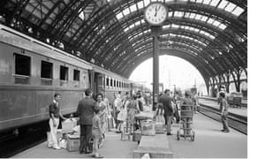 Passengers wait to board the Rome Express at Milan Central Station July 1962