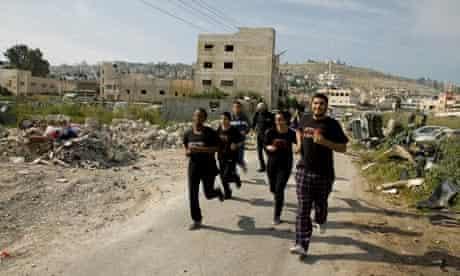 drama students run through Jenin refugee camp