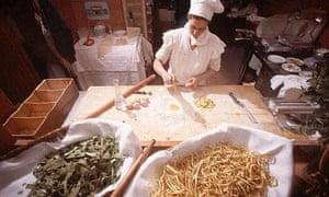 Chef Making Pasta Beside Pasta on Display