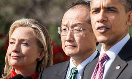 Secretary of State Hillary Clinton and Jim Yong Kim listen while President Barack Obama speaks.