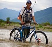 Peru farmers wheels bicycle across swollen stream