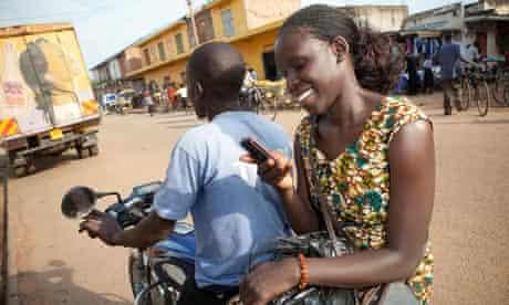 Ugandan woman texts on motorcycle taxi