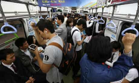 commuters on smartphones in South Korea