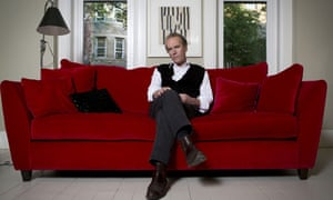 Martin Amis sitting on red sofa, at home in New York