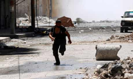 A man runs for cover during clashes in Aleppo