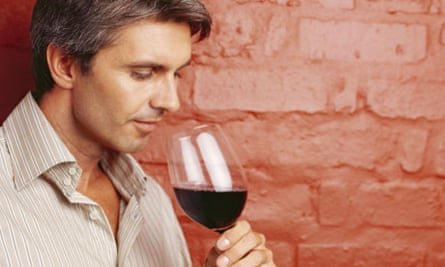side profile of a mid adult man drinking a glass of red wine