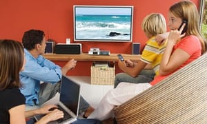 Parents and two teenagers watching television