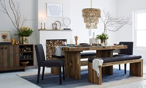 Dining table with benches and chandelier set up in a room