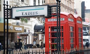 Ladies toilet sign and red phone box in London