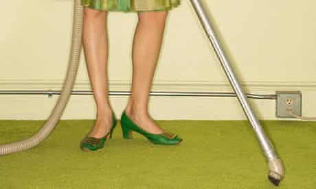 Legs of woman with green shoes and dress hoovering green carpet