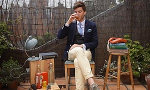 Man in suit and tie with crossed legs drinking on a roof terrace