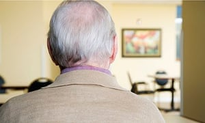 an elderly man looking at a picture