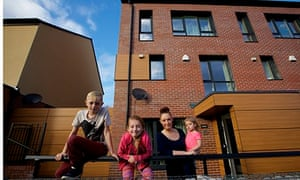 Justine Hutton and her children pose outside their passive house in Oldham