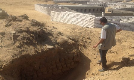 An archaeologist looks into a fresh tomb