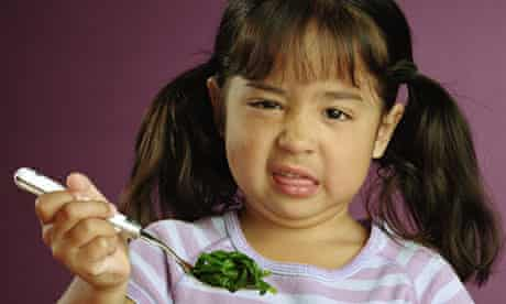 Girl making face at spinach