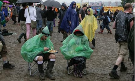 People sitting in rain ponchos in the mud at Glastonbury
