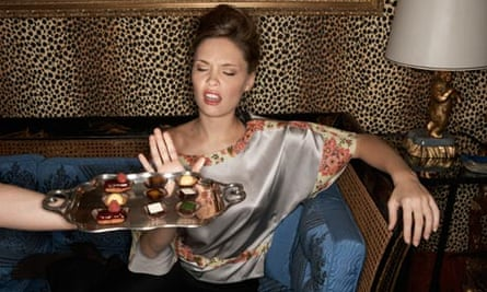 woman waves away tray of chocolates