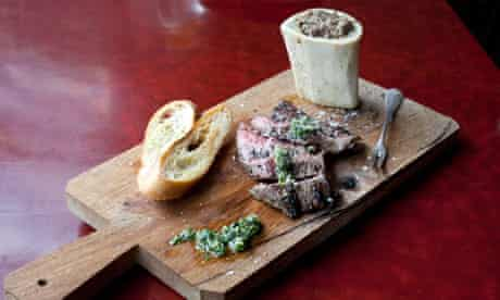Bavette steak with marrowbone and bread on a board