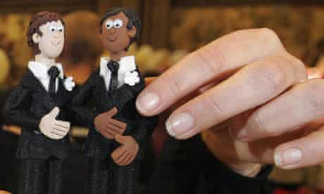 Male wedding-cake figures held by a woman's fingers
