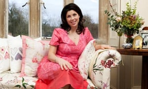TV presenter Kirstie Allsopp sitting on a sofa, ankles crossed