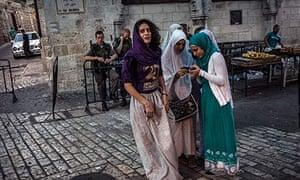 Arab women watched by Israeli soldiers in Jerusalem